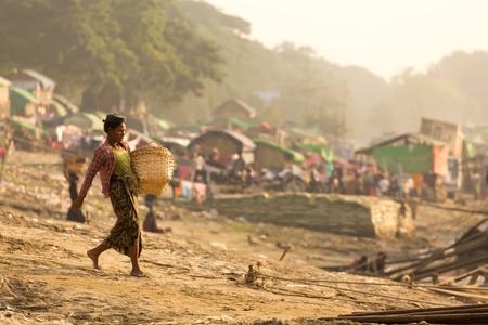 mundo contaminado: Mandalay, Myanmar, 17 de Enero, 2015: Una mujer lleva una cesta, waling sobre un terreno en pendiente y va a descargar un barco de tablones de madera en una barriada cerca del río en Mandalay, Myanmar (Birmania).