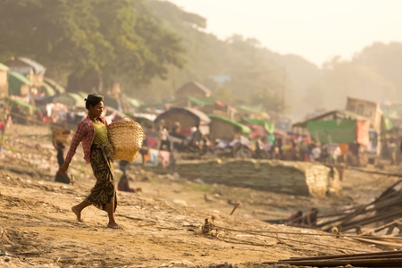 sloping: MANDALAY,MYANMAR,JANUARY 17, 2015 : A woman is carrying a basket , waling on a sloping ground and going to unload a boat of wooden planks in a slum area near the river in Mandalay, Myanmar (Burma).