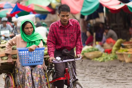 sidecar: MANDALAY,MYANMAR,JANUARY 17, 2015 : A couple of vegetable seller is riding a sidecar bicycle in the muddy street of the Zegyo outdoors market, in Mandalay, Myanmar (Burma).