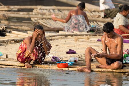 slum: MANDALAY,MYANMAR,JANUARY 19, 2015 : Women taking shower and washing dishes in a slum area at the Irrawaddy river in Mandalay, Myanmar (Burma). Editorial