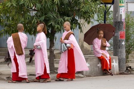nuns: MANDALAY,MYANMAR,JANUARY 17, 2015: A group of young Buddhist nuns is walking in the streets of Mandalay, Myanmar (Burma).
