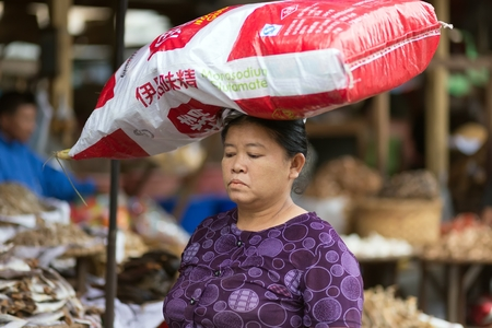glutamate: MANDALAY,MYANMAR,JANUARY 17, 2015 : A woman is carrying a large monosodium glutamate bag on her head in the street of Mandalay, Myanmar (Burma).
