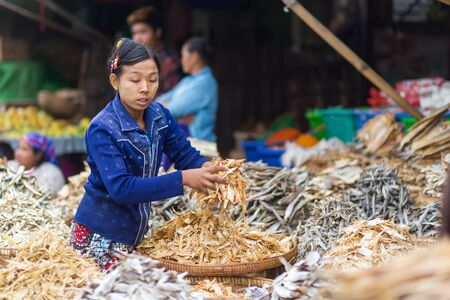 squatting down: MANDALAY,MYANMAR,JANUARY 17, 2015: A  woman is selling dry fish in the central street market of Zegyo, in Mandalay, Myanmar (Burma). Editorial