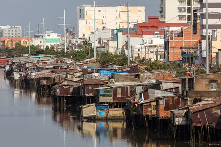 shanty: Slum wooden house on the Saigon river bank, in front of modern buildings, in Ho Chi Minh city, Vietnam Editorial