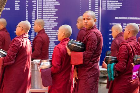 queueing: AMARAPURA, MYANMAR, JANUARY 20, 2015 : Monks are queueing holding their bowls to collect the unique daily meal at noon in the Mahagandayon monastery near Mandalay, Myanmar (Burma).