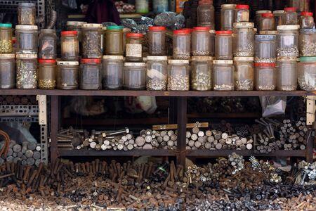 hardware: tornillos ordenados, tuercas y tornillos en una ferretería ambulante vietnamita Foto de archivo