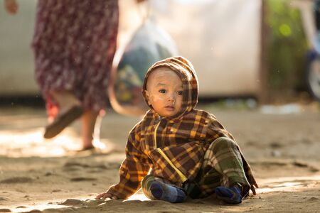 snot: BAGAN, MYANMAR, JANUARY 24, 2015: A Burmese little child is sitting in a dirty street of the old Bagan village in Myanmar (Burma) Editorial