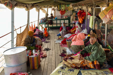 bedcover: BAGAN, MYANMAR, JANUARY 22, 2015 : The Burmese passengers are waking up in the morning on the boats deck going from Mandalay to Bagan in Myanmar (Burma). Editorial