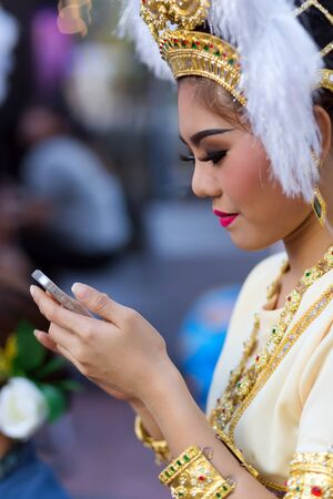 krung: BANGKOK, THAILAND, February 17, 2015 : A Thai lady traditional dancer is checking her smartphone before the show celebrating the new Krung Kasem floating market in Bangkok, Thailand