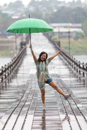sangkhla buri: Woman dancing in the rain falling on the Mon wooden bridge of Sangklaburi, Thailand Stock Photo