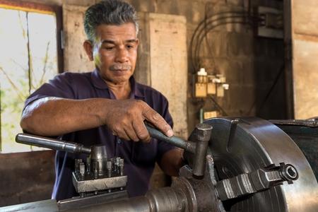 turner: Thai mechanic turner using machinery in his workshop, focus on the hand. Stock Photo