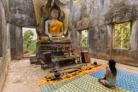 sangkhla buri: Thai woman praying in the ancient hidden temple of Wat Som Ded in Sangkhlaburi, Thailand Editorial
