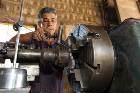 machinery machine: Thai mechanic turner using machinery in his workshop, focus on the machine.