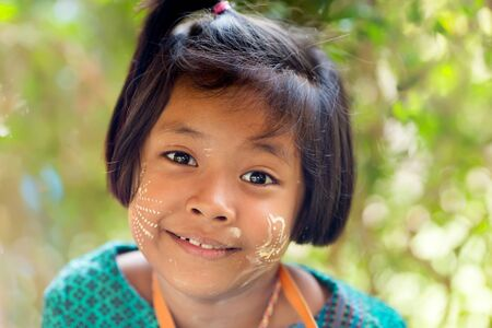 impish: SANGHLABURI, THAILAND, JANUARY 24, 2016 : A Thai little girl selling souvenir stuffs is posing near a temple in Sanghlaburi, Thailand