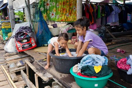 ao: AO SALAT, THAILAND, JANUARY 31, 2016 : Two sisters are hand washing the family laundry in front of the home in Ao Salat fishing village, Ko Kood island, Thailand