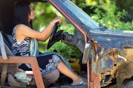 Woman driving damaged and rusted car Stock Photo