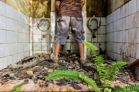latrine: Man peeing in ruined and abandoned  tropical toilets Stock Photo