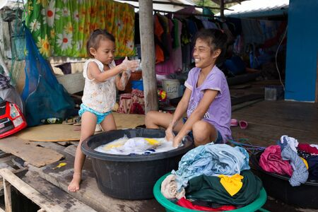 handwashing: AO SALAT, THAILAND, JANUARY 31, 2016 : Two sisters are hand washing the family laundry in front of the home in Ao Salat fishing village, Ko Kood island, Thailand