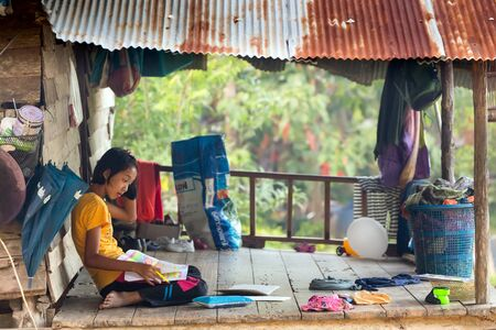KO MOOK ISLAND, THAILAND, JANUARY 06, 2016 : A young girl is doing her homework, sitting outside on the home wooden floor in Ko Mook island, Thailand