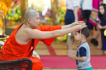 wiwekaram: SANGKHLABURI, THAILAND, JANUARY 24, 2016 :  A buddhist monk is blessing a little boy  by inserting a rosary necklace around his neck in the Wat Wang Wiwekaram temple, Sanghklaburi, Thailand