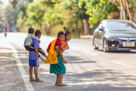 SANGHLABURI, THAILAND, JANUARY 24, 2016 : Kids are carrying little brothers on their back for crossing the road in Sangkhlaburi, Thailand Redakční