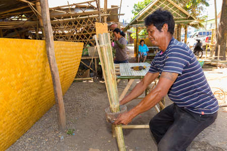 cleave: TRANG, THAILAND, JANUARY 11, 2016 : Craftsman splitting a bamboo with a special tools for building a wooden table in Trang, Thailand Editorial