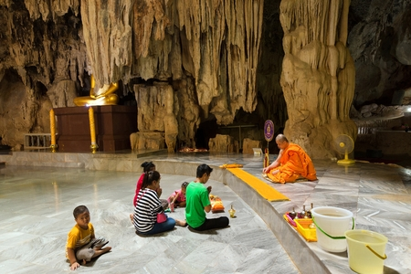 in wa: KANCHANABURI, THAILAND, JANUARY 19, 2016 : A thai family is praying and meditating with a Buddhist monk in the Wat Tham Pu Wa cave temple in Kanchanaburi, Thailand
