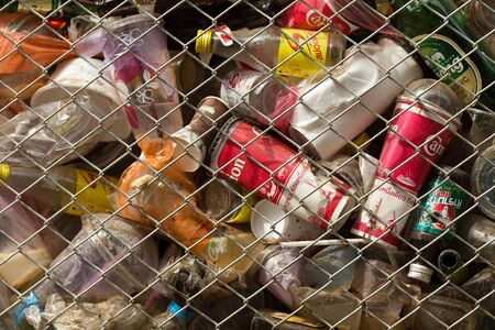 fenced in: SANGHLABURI, THAILAND, JANUARY 24, 2016 : A fenced public bin is full of soda cans, glass bottel and other drinks in Sangkhlaburi, Thailand Editorial
