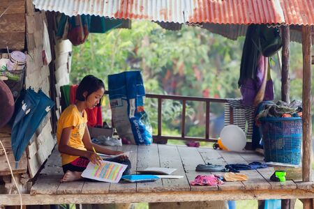 mook: KO MOOK ISLAND, THAILAND, JANUARY 06, 2016 : A young girl is doing her homework, sitting outside on the home wooden terrace in Ko Mook island, Thailand Editorial