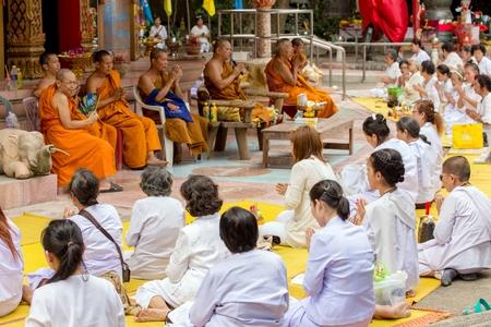 chanting: NAKHON PATHOM, THAILAND, JANUARY 16, 2016 : Buddhist monks and women are chanting and praying outside the Wat Samphran temple in Nakhon Pathom near Bangkok, Thailand Editorial