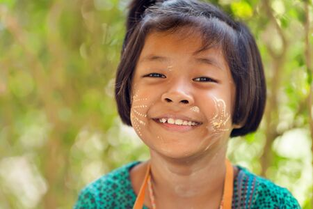 thanaka: SANGHLABURI, THAILAND, JANUARY 24, 2016 : A Thai little girl with Burmese Thanaka cosmetic powder is posing near a temple in Sanghlaburi, Thailand