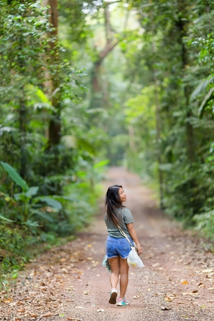 kood: Woman walking and looking back in a jungle path  in the Ko Kood island in Thailand