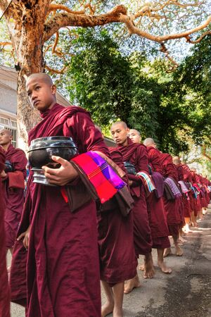 rigor: AMARAPURA, MYANMAR, JANUARY 20, 2015 : Young monks are queuing holding their bowls to collect the unique daily meal at noon in the Mahagandayon monastery near Mandalay, Myanmar (Burma).
