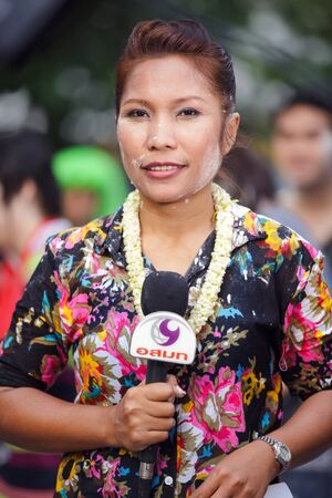 tv reporter: BANGKOK, THAILAND, APRIL 13, 2011 : A TV reporter woman is talking holding her microphone in the Silom road about the Songkran Buddhist festival in Bangkok, Thailand. Editorial