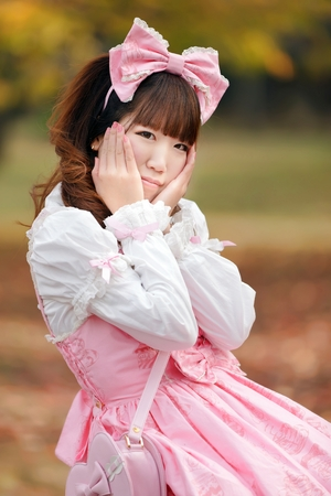 lolita: Portrait of Japanese in sweet lolita cosplay holding his head Stock Photo