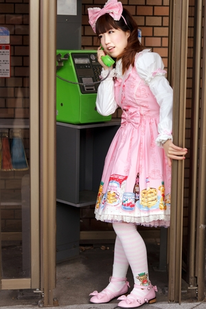 lolita: Japanese lolita dressed in pink lolita cosplay is calling in a phone public booth Stock Photo
