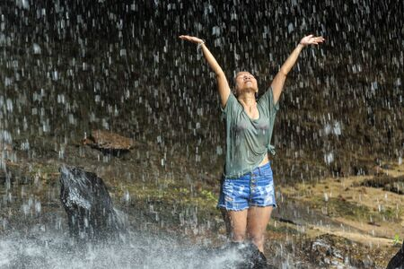 rain wet: Joyful dressed woman under tropical waterfall, Thailand