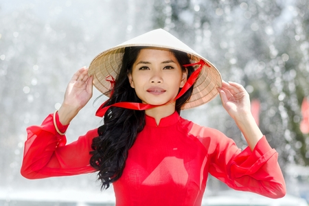 ao: Vietnamese woman in a traditional red outfit and conical hat standing in front of a fountain