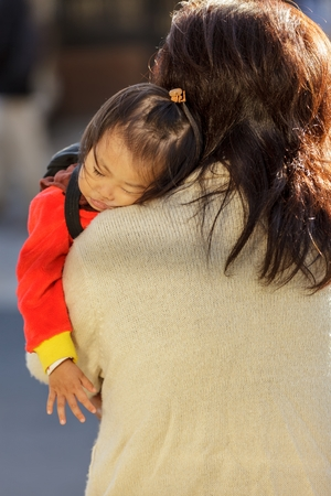 shoulder carrying: KYOTO, JAPAN, NOVEMBER 20, 2011 : A mother is carrying her sleeping little daughter on her shoulder in a street of Kyoto, Japan