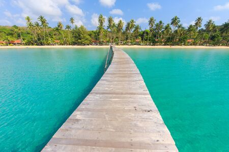 Wooden pontoon in the turquoise tropical sea of Ao Phrao beach in Ko Kood island, Thailand .