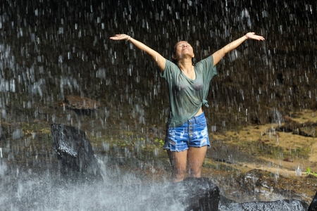 rain wet: Happy dressed woman overstretching her arms under tropical waterfall, Thailand