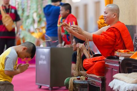 wiwekaram: SANGKHLABURI, THAILAND, JANUARY 24, 2016 :  A skilled Buddhist monk is blessing a man  by throwing a rosary necklace around his neck in the Wat Wang Wiwekaram temple, Sanghklaburi, Thailand