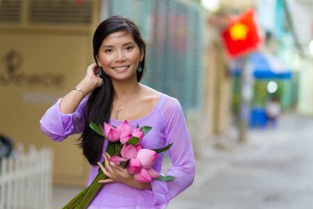 Vietnamese woman holding lotus flowers bud bunch Stock Photo