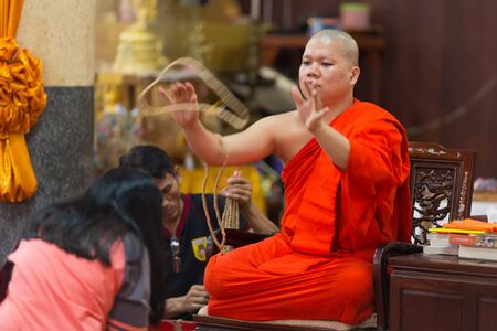 wiwekaram: SANGKHLABURI, THAILAND, JANUARY 24, 2016 : A skilled Buddhist monk is blessing a woman by throwing a rosary necklace around his neck in the Wat Wang Wiwekaram temple, Sanghklaburi, Thailand