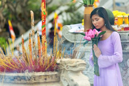Pretty Vietnamese girl praying as she makes an offering of fresh flowers at a Buddhist shrine during an open air ceremony Stock Photo