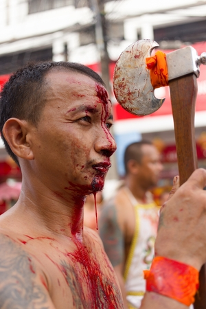devotee: PHUKET TOWN, THAILAND, OCTOBER 09, 2016 : Taoist devotees self harming with an axe for purification during vegetarian festival in Phuket town, Thailand