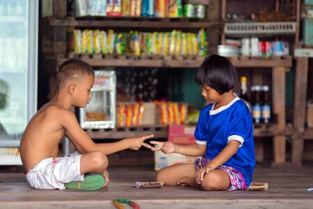 finger shape: AO YAI, THAILAND, JANUARY 30, 2016 : Two little boys sitting on a floor in a store are playing roshambo rock paper scissor game in the Ao Yai fishing village, Ko Kood island, Thailand