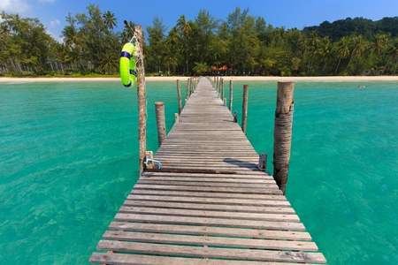island paradise: Wooden pontoon in the turquoise tropical sea of Ao Phrao beach in Ko Mook island, Thailand .