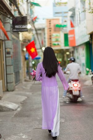 lotus flowers: Vietnamese woman walking in Ho Chi Minh street wearing Ao Dai traditional dress, carrying lotus flowers with the Vietnam flag in background .