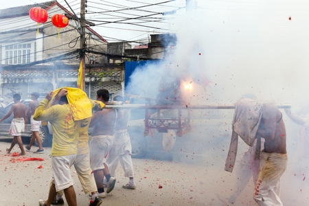 palanquin: PHUKET TOWN, THAILAND, OCTOBER 09, 2016 : Taoist devotees are carrying palanquin containing an idol, under heavy firecrackers explosions during vegetarian festival in Phuket town, Thailand